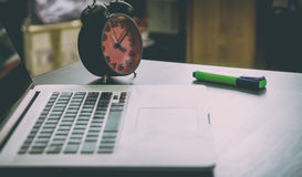 Computer Laptop on Office table alarm clock Royalty Free Stock Images