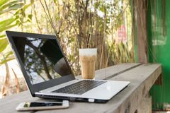 Computer laptop and smart phone and fresh coffee cappuccino. On wooden table of brown in coffee shop Stock Photo