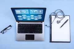 Computer laptop, stethoscope and clipboard. With blank paper sheet on the table Royalty Free Stock Images