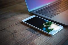 Computer-Laptop und weißer Handy mit Tablette auf hölzernem Vorsprung lizenzfreies stockbild