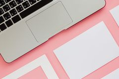 Computer laptop with white frame and paper cards on pink color b. Ackground for workspace concept. Flat lay and top view image stock photos
