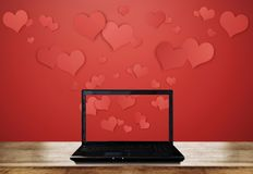 Computer laptop on wooden desk with floating hearts on red background. S Stock Photo