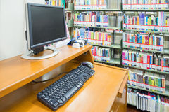 Computer in a library with many books and shelves in the backgro. Und Stock Image