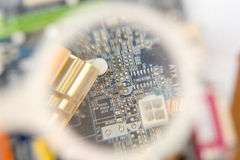 Computer mainboard under magnifier stock image