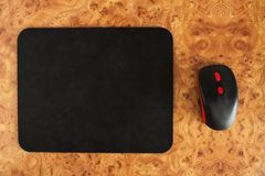 Computer mat and computer mouse on a brown patterned background, close-up, optical stock images