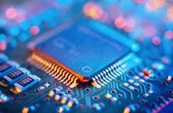 Computer Microchips and Processors on Electronic circuit board. Abstract technology microelectronics concept background. Macro shot, shallow focus royalty free stock image