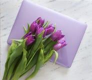 Computer mit Blumenstrauß von purpurroten Tulpen Lizenzfreies Stockbild