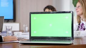 Computer mit der grünen Schirmfarbenreinheit Schein oben auf einer Tabelle im Konferenzsaal stock video footage