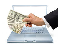 Computer Money Internet Transaction. A business mans hand holding American money over an isolated laptop computer Stock Images
