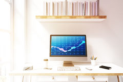 Computer monitor with a blue graph. Close up of a computer monitor standing on a desk near a lamp and a notebook. There is a blue graph on the screen. Concept of Royalty Free Stock Photos