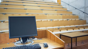 Computer monitor with empty seats in a lecture hall Royalty Free Stock Photo
