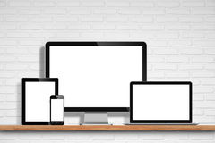 Computer monitor, laptop, tablet pc and mobile phone. With blank screen on the table with white brick wall background Stock Image