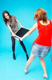 Computer Monitor Tug Of War. Two teenage girls struggling over a blank computer monitor between them. Held by both girls with both hands. Girl facing the camera royalty free stock images