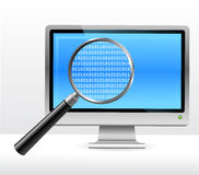 Computer monitor under magnifying glass Royalty Free Stock Photography