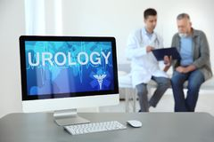 Computer monitor with word UROLOGY. And blurred people on background stock photo