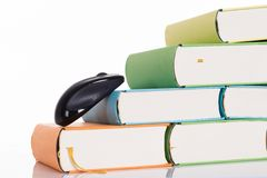 Computer mouse climbing books Royalty Free Stock Image