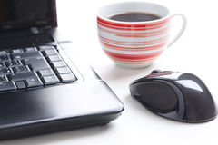 Computer mouse and coffee cup Stock Photos