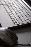 Computer mouse next to a laptop and glasses Stock Photos
