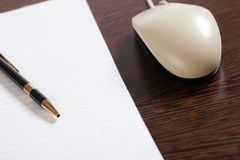 Computer mouse and pen with paper Stock Images