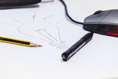 Generating new ideas. Computer, mouse, pencil and pen are on the white desk of an office where there is the drawing of a bulb lighted on, symbol of the new ideas Stock Photos
