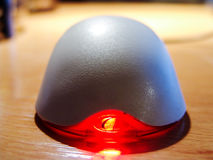 Computer mouse on a table with a red glowing diode. Front view Stock Image