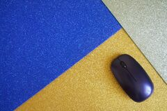 A computer mouse on three shiny multi-colored mousepad - gold, blue and silver. Technology, sales and diversity