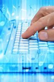 Computer Music Technology Download. A computer with a hand pressing the keys with music notes floating around Stock Photography