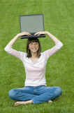 Computer on my head. Teenager working at computer on the grass Royalty Free Stock Photography