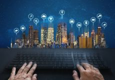 Computer networking and internet connection. Hand typing computer keyboard and buildings with social networking and application ic stock image
