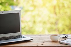 Computer with notebook, glasses and cup of tea or coffee on wooden table and nature background stock image