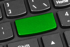 Computer notebook keyboard with blank green key. Technology background stock image