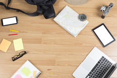 Computer notebook, notepad and map on wooden table Royalty Free Stock Photo
