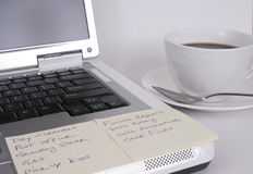 Computer with notes and cup of coffee. Notebook computer with notes attached and a cup of coffee on a white background Stock Photography
