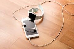 Computer, orologio astuto, telefono, cuffia con fondo di legno Immagine Stock