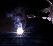 Computer part welding. Symbolic scenery showing the welding of a hard disk drive in dark back Stock Photography