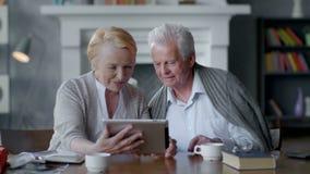 Computer pensionato adorabile felice della compressa di uso delle coppie Essi che si divertono nella comunicazione con la famigli video d archivio