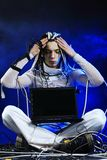 Computer person. Shot of a futuristic young man sitting with a laptop and wires Royalty Free Stock Image