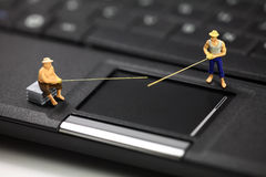Computer phishing and identity theft concept. Miniature fisherman standing on a laptop representing online email phishing scams. Online phishing and identity Royalty Free Stock Images