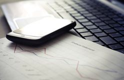 Computer and phone. Close up of laptop with financial statement and mobile phone Royalty Free Stock Image