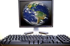 Computer. Planet Earth on the computer screen and keyboards on white Royalty Free Stock Image