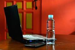 Computer portatile, acqua potabile in bottiglia e Smartphone Immagini Stock Libere da Diritti