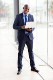 Computer portatile africano dell'uomo d'affari Immagine Stock