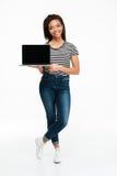 Computer portatile africano sorridente dello schermo in bianco di condizione e della tenuta della donna dei giovani Fotografia Stock Libera da Diritti