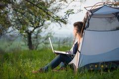 computer portatile all'aperto che usando i giovani della donna Immagini Stock