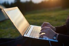 computer portatile all'aperto che usando i giovani della donna Fotografie Stock