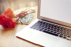 Computer portatile aperto con spazio per la disposizione su una tavola di legno nella barra del caffè, fiori dei biglietti di S.  Immagini Stock