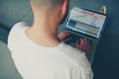 Computer portatile aperto di seduta della parte anteriore dell'uomo d'affari con informazioni finanziarie come i grafici e grafic Immagine Stock Libera da Diritti