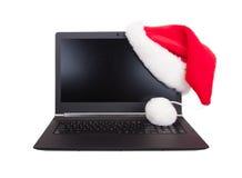 Computer portatile aperto moderno con il cappello rosso del Babbo Natale messo sull'angolo dell'affissione a cristalli liquidi Fotografia Stock Libera da Diritti