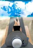 Computer portatile asiatico del gioco di stile di vita delle donne e rilassarsi vicino al sunbath di lusso della piscina, giorno  Fotografia Stock