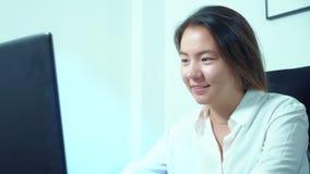 Computer portatile asiatico sveglio di uso della ragazza alla tavola in ufficio archivi video